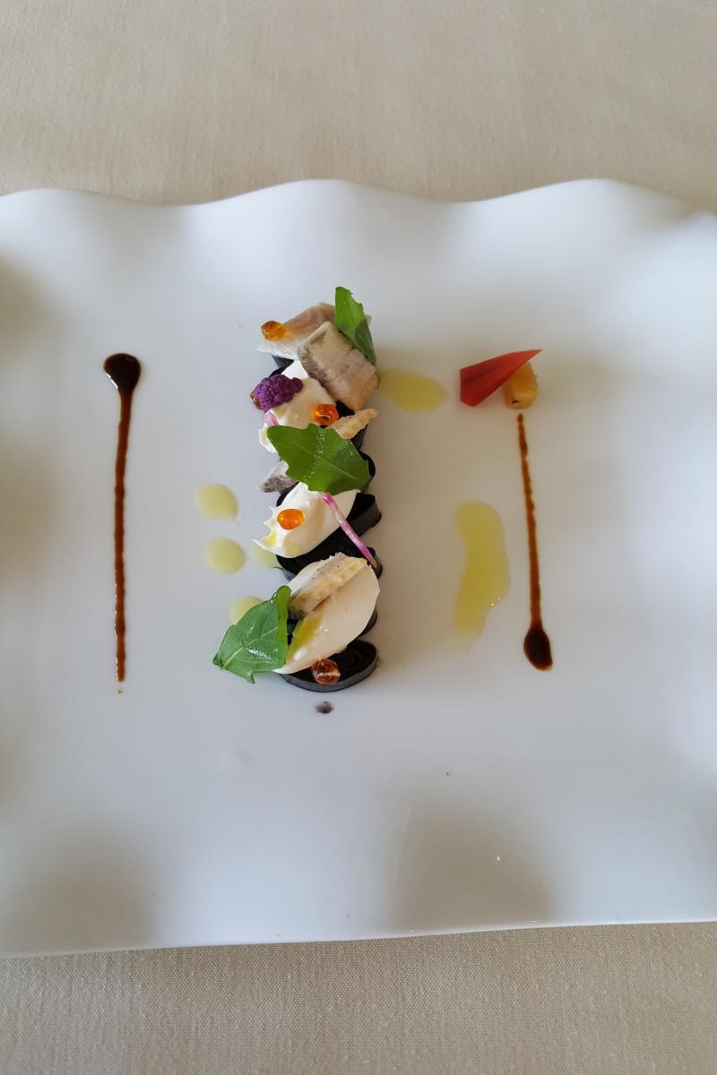 poireau cuit à basse température à l'encre de seiche, anguille fumée