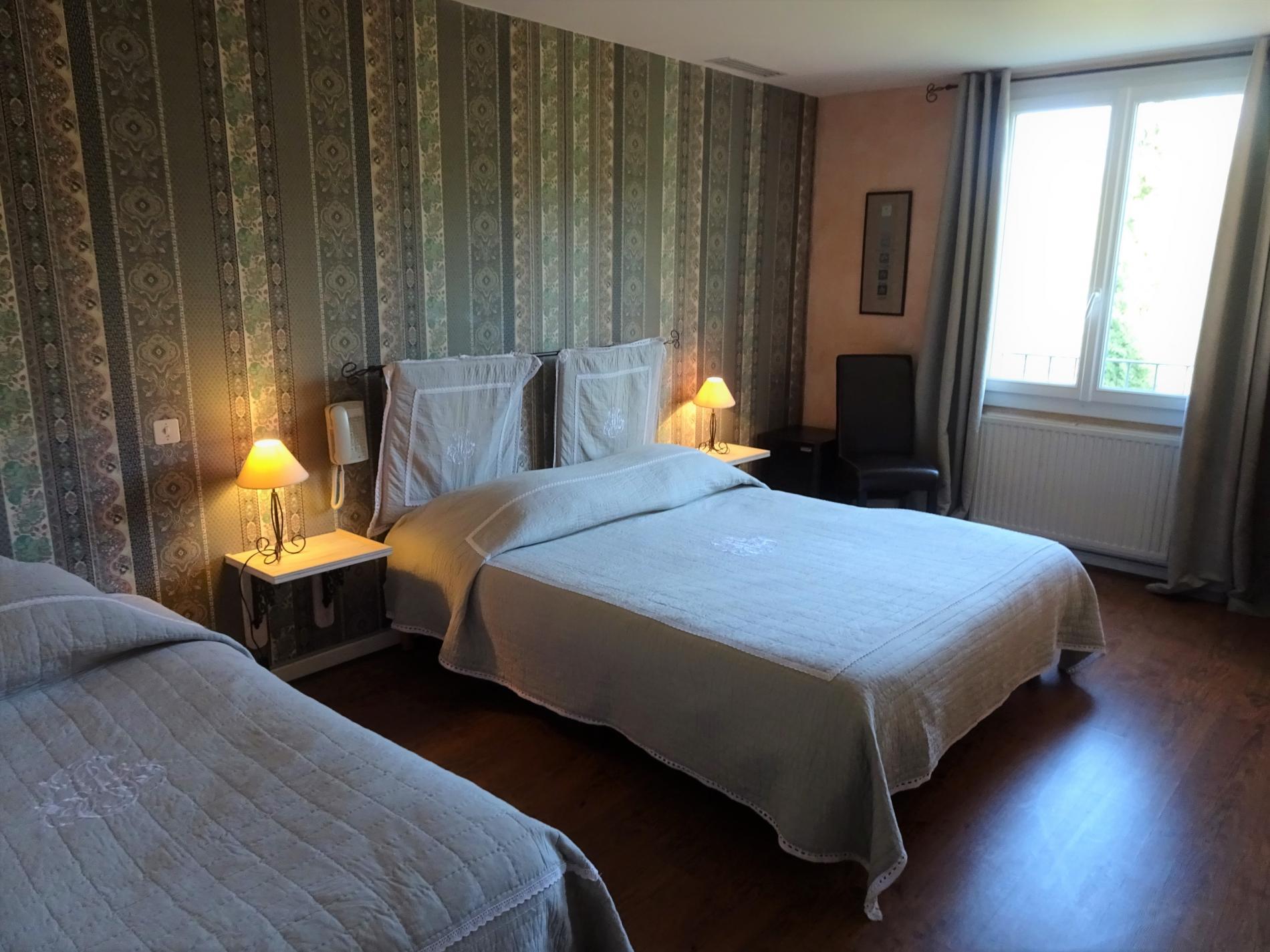 Chambre d'hôtel avec grand lit, lit simple et vue parc