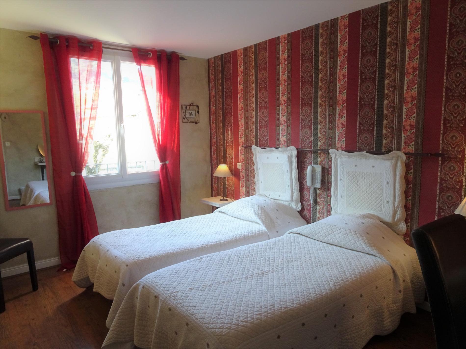 Chambre d'hôtel avec lits jumeaux et vue village