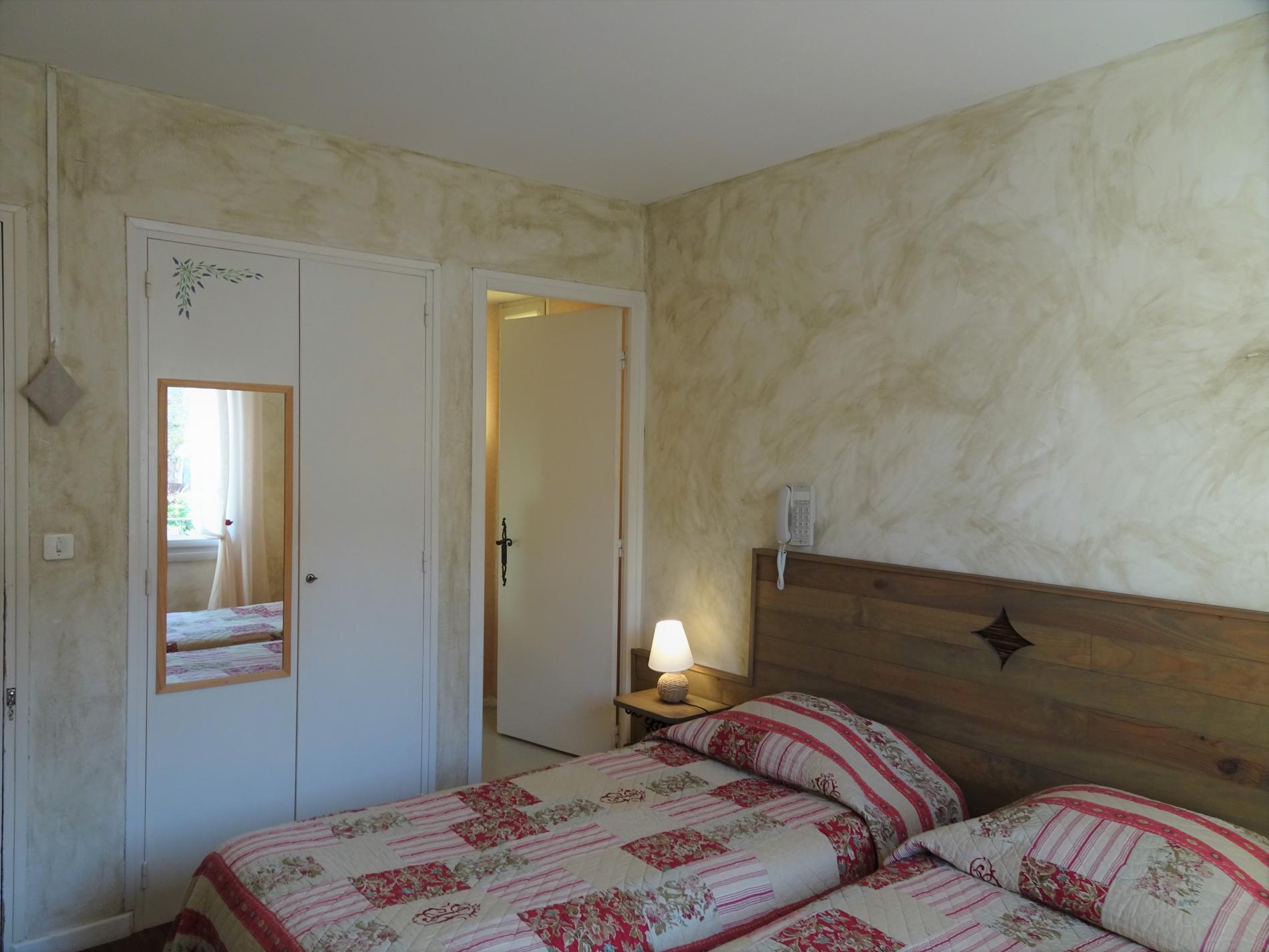 Chambre d'hôtel avec grand lit et vue village
